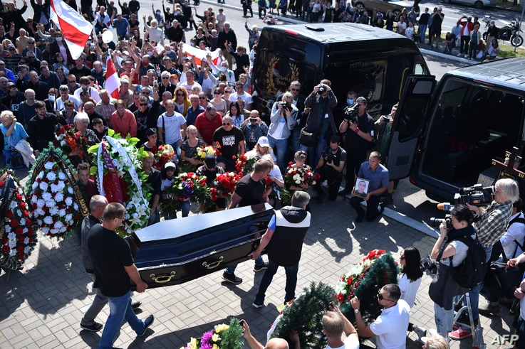 Men carry a coffin with the body of Alexander Taraikovsky, a 34-year-old demonstrator who died Aug. 10, 2020, amid clashes while protesting election results, during his funeral ceremony in central Minsk, Belarus, Aug. 15, 2020.