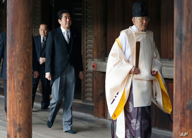 FILE - Japanese Prime Minister Shinzo Abe, center, follows a Shinto priest to pay respect to the war dead at Yasukuni Shrine in Tokyo, Japan, Dec. 26, 2013.