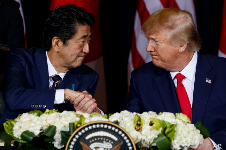 FILE - Japanese Prime Minister Shinzo Abe, left, shakes hands with President Donald Trump before signing a trade agreement on the sidelines of the United Nations General Assembly, in New York City, Sept. 25, 2019.