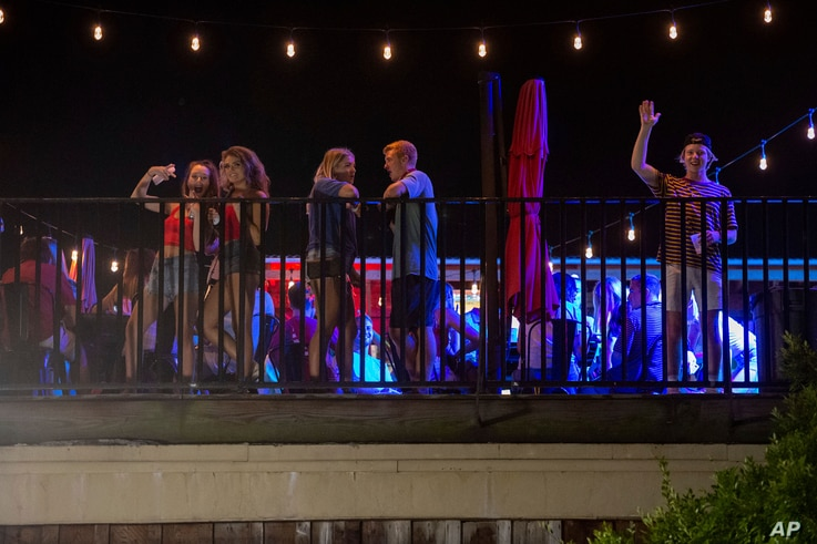 Patrons stand on the Bear Trap's rooftop bar on The Strip, the University of Alabama's bar scene, Aug. 15, 2020, in Tuscaloosa, Alabama.