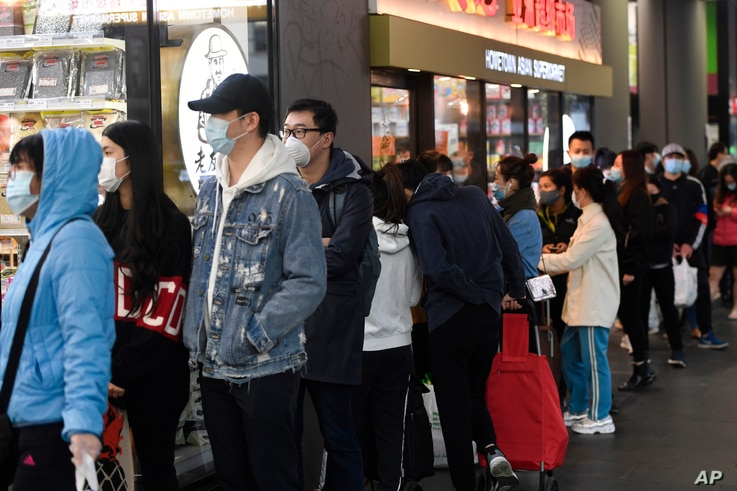 People line up to enter a supermarket hours before a citywide curfew is introduced in Melbourne, Australia, Aug. 2, 2020.
