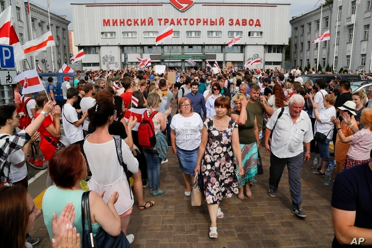 Workers of the Minsk Tractor Works Plant leave after their work shift as activists with old Belarusian national flags greet them in Minsk, Belarus, Aug. 18, 2020.