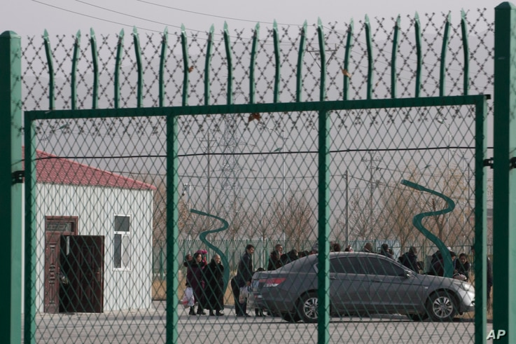 FILE - Residents line up inside a vocational training center in Artux, in western China's Xinjiang region, Dec. 3, 2018. Critics say China uses some of these facilities as detention camps for forced labor.
