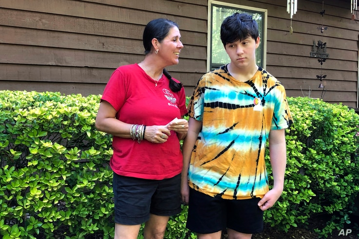 Molly Ball talks to her son Henry about plans to send him back to in-person classes this fall, as they stand outside their house in Woodstock, Ga., July 23, 2020.