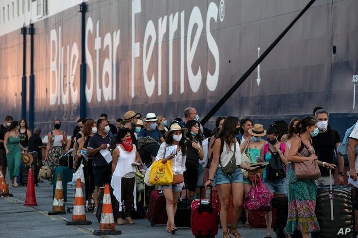 Passengers wait to board a ship bound to Greek Aegean islands at the port of Piraeus, near Athens, Greece, Aug. 1, 2020.