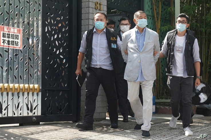 Hong Kong media tycoon Jimmy Lai, center, who founded local newspaper Apple Daily, is arrested by police officers, Aug. 10, 2020.