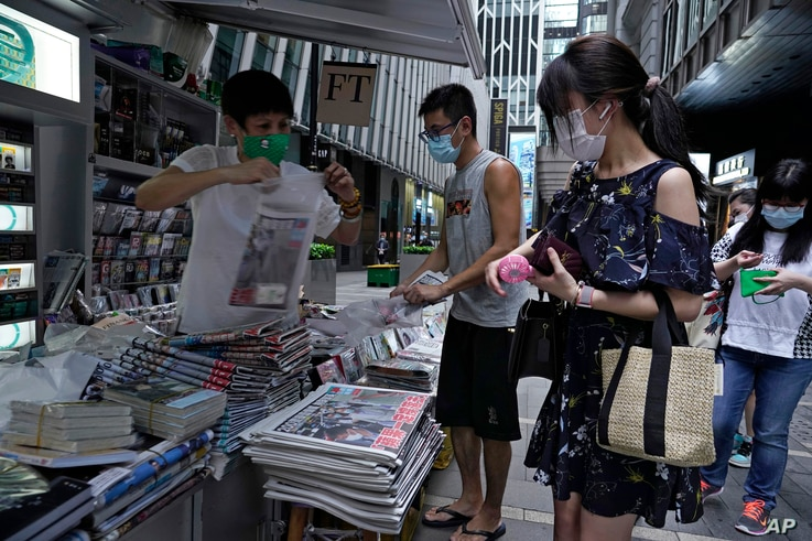 People queue up at a news stand to buy copies of Apple Daily in downtown Hong Kong, Aug. 11, 2020, as a show of support, a day after the arrest of its founder Jimmy Lai.