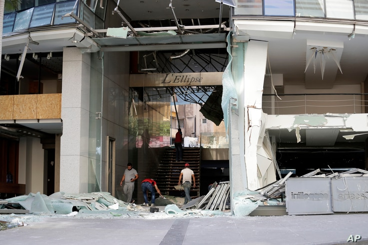 People are seen at the entrance to a damaged building near the site of an explosion Tuesday that hit the seaport of Beirut, Lebanon, Aug. 6, 2020.