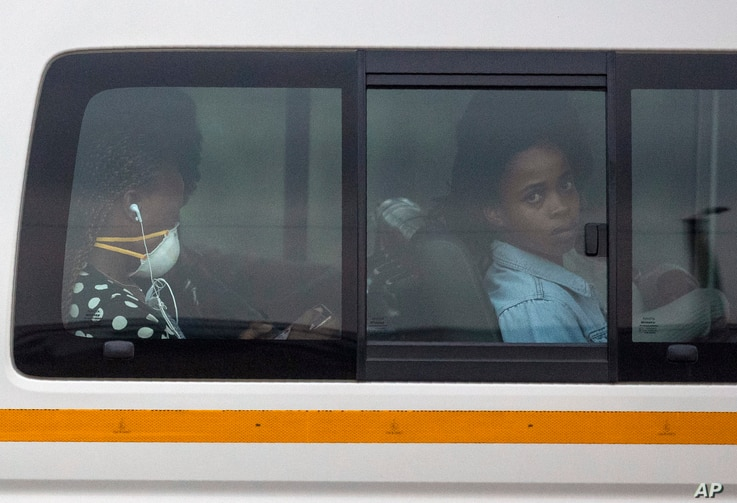 FILE - Passengers sit inside a minibus taxi during their trip home, in Kwa-Thema, east of Johannesburg, South Africa, March 17, 2020.