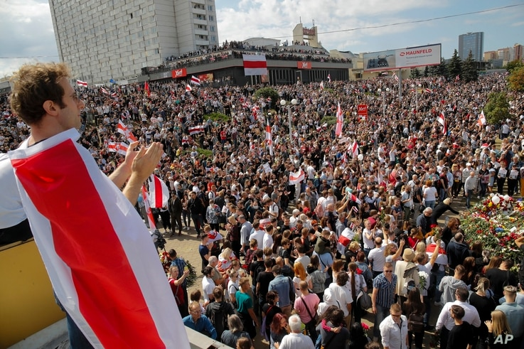 People hold old Belarusian national flags while gathered at the place where Alexander Taraikovsky died during clashes protesting election results, in Minsk, Belarus, Aug. 15, 2020.