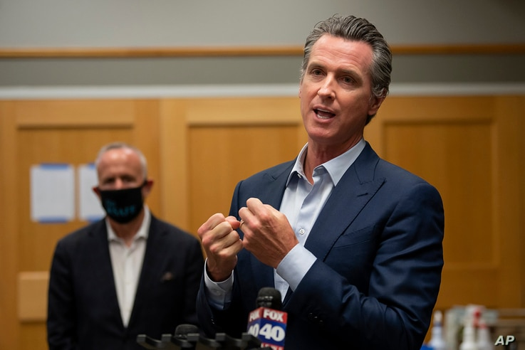 FILE - California Governor Gavin Newsom, right, speaks during a tour of a cooling center in Sacramento, California, Aug. 18, 2020. Newsom declared an emergency Tuesday over wildfires burning throughout the state.