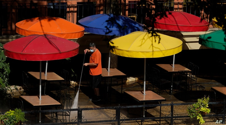 FILE - A worker wearing a mask to protect against the coronavirus power-washes an exterior dining area along the River Walk, in San Antonio, Texas, Aug. 12, 2020.
