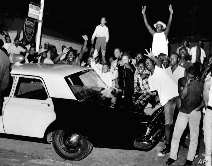 FILE - Demonstrators push against a police car in the Los Angeles area of Watts, Aug. 12, 1965.