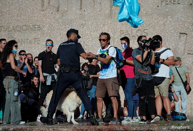 A police officer confronts a protester at a rally against the use of protective masks amid the coronavirus pandemic, in Madrid, Spain, Aug. 16, 2020.