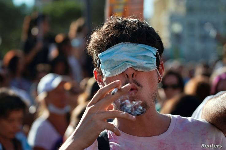 A man smokes a cigarette with his eyes covered by a face mask as he takes part in a protest against the use of protective masks amid the coronavirus pandemic, in Madrid, Spain, Aug. 16, 2020.