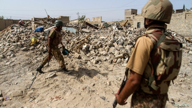 Pakistani soldiers stand near the debris of a house which was destroyed during a military operation against Taliban militants…