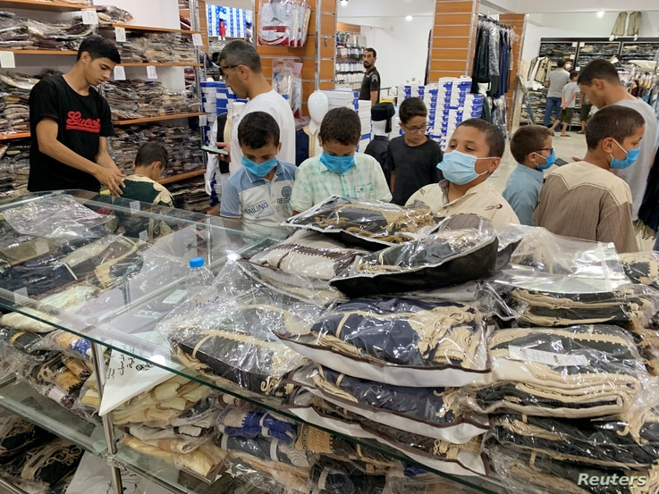 Children wear protective face masks as they look at clothes in a shop ahead of the Eid al-Adha celebrations amid the coronavirus disease (COVID-19) pandemic, in Misrata, Libya, July 28, 2020.