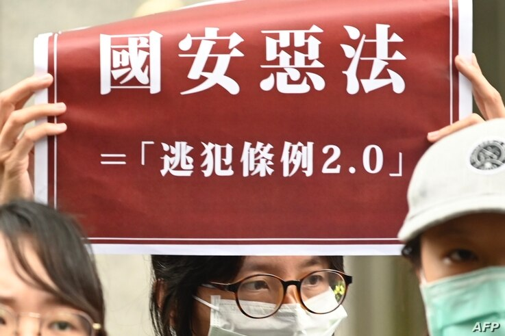 "Students from Hong Kong and Taiwan display placards reading ""Bad laws of China's national security"" during a protest outside…"