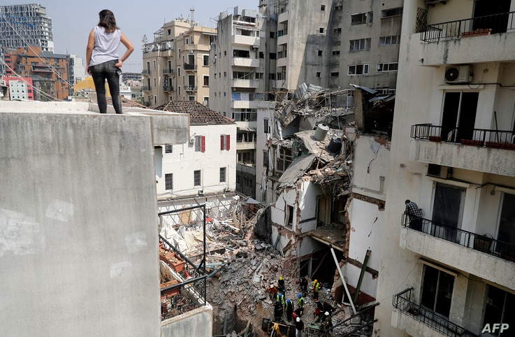 A woman looks on from a rooftop as rescue workers dig through the rubble of a badly damaged building in Lebanon's capital…