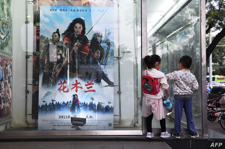 "Children play next to a poster of the Disney movie ""Mulan"" outside a cinema in Beijing on September 11, 2020. - Pilloried…"