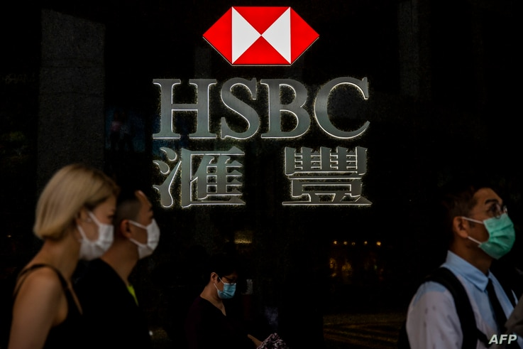 Pedestrians walk past a HSBC logo in Hong Kong on September 21, 2020. - Shares in banking giant HSBC plunged to a 25-year low…