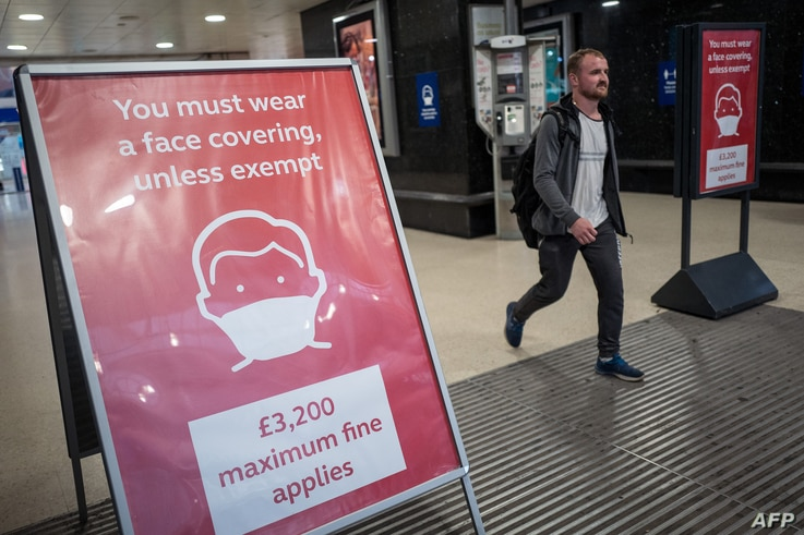 A man, not wearing a face covering, passes signs telling travellers they must wear face mask unless they are exempt, as he…