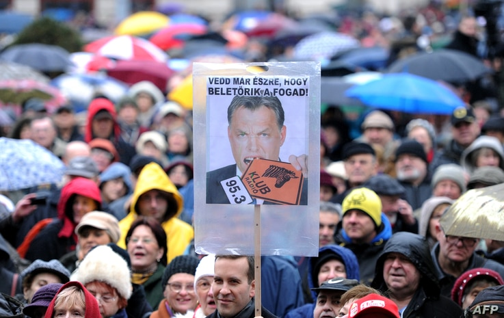 Employers of Hungary's opposition radio, the 'Klubradio' and their sympathizers hold umbrellas with a photo of Hungarian Prime…