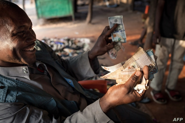 Issouf Zacharia, a 47-years-old merchant in Birao, northern Central African Republic, shows Sudanese bank bills on December 20,…