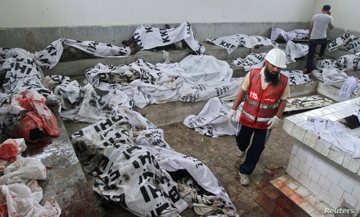 A rescue worker walks past covered bodies, killed during a fire at a garment factory, after they were brought to the Jinnah…