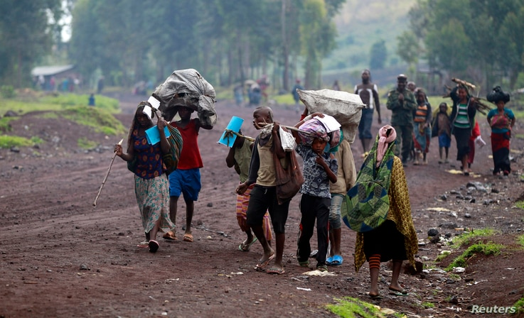 Civilians displaced by recent fighting between Congolese army and M23 rebels carry their belongings as they walk along a road…