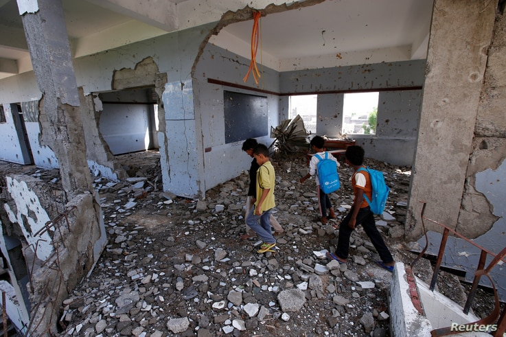 Boys walk in their school damaged by a recent Saudi-led air strike, in the Red Sea port city of Hodeidah, Yemen October 24,…