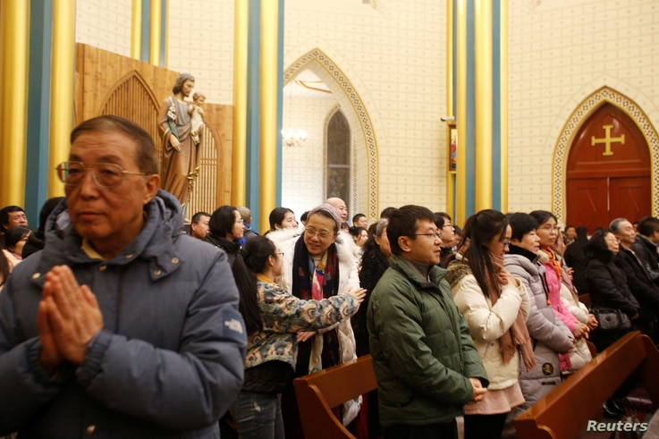 Worshippers attend a mass at Xishiku Cathedral, a government-sanctioned Catholic church, on Christmas Eve in Beijing, China…