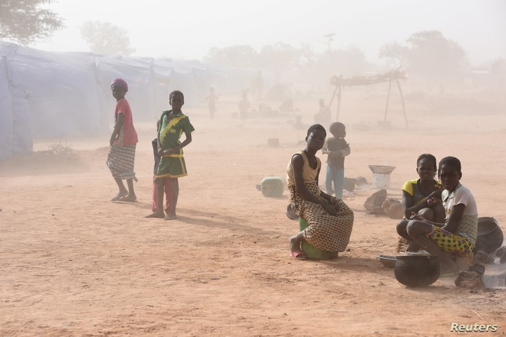 Displaced people, who fled from attacks of armed militants in Roffenega, are engulfed in dust as they sit at the camp built by…