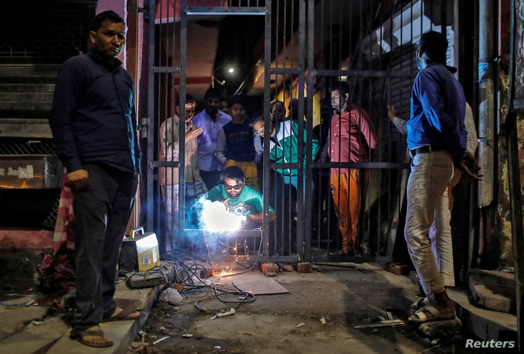 Mulsims erect a steel gate in a lane following Hindu-Muslim clashes triggered by a new citizenship law, in Chand Bagh in the…