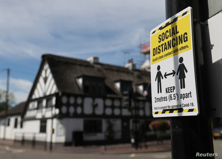 A sign promoting social distancing is hung on a post near the Crown and Anchor pub following a spike in cases of the…