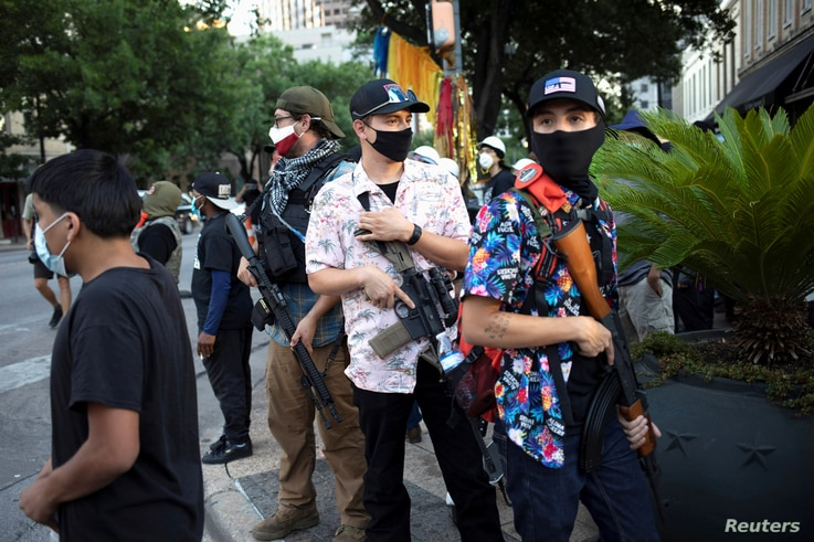 A Texas Guerrillas member who calls himself, 'Apex,' third from right, and others carry weapons at a Black Lives Matter rally...