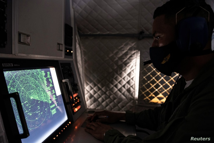 An Ecuadorian navy officer looks at a radar after a fishing fleet of mostly Chinese-flagged ships was detected in an…