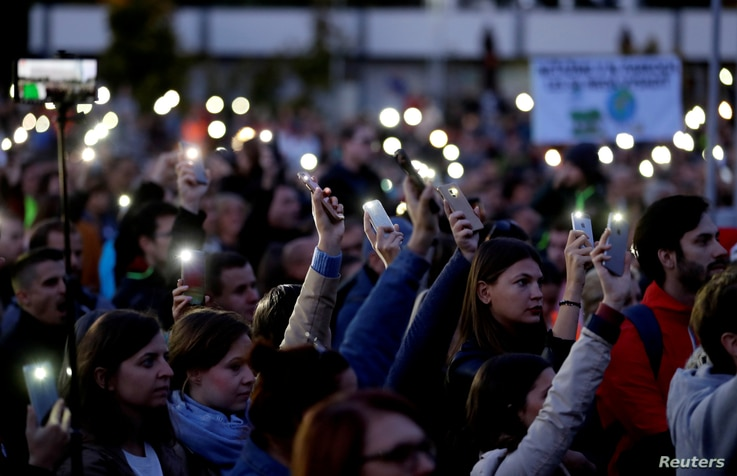 FILE PHOTO: Demonstrators light up their mobile phones as they  attend an anti-government protest rally in reaction to last…