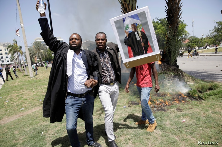 Men carry a picture depicting lawyer and President of the Bar of Lawyers of Port-au-Prince Monferrier Dorval, who was murdered.