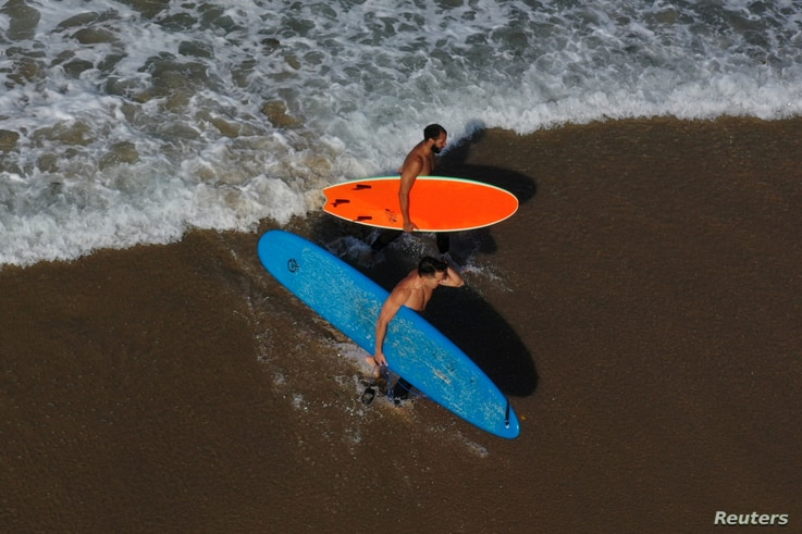 Surfers walk out of the Pacific Ocean on the first day of a record heat wave, amid the global outbreak of coronavirus disease …