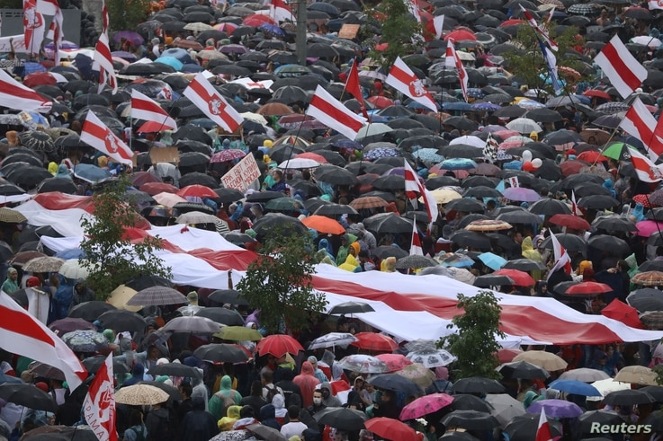 People take cover from rain under umbrellas during an opposition rally to protest against police brutality and to reject the…
