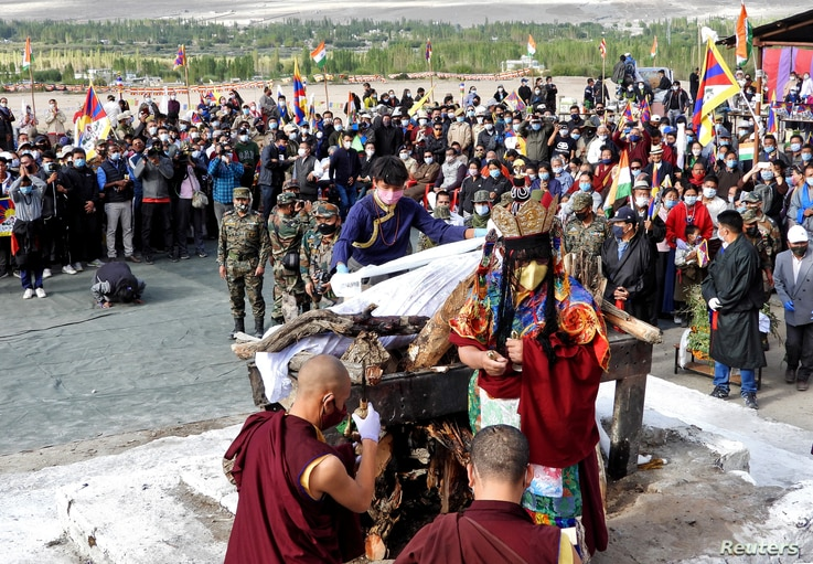 A relative places khadaks, a white piece of silk cloth, over the pyre of Tenzin Nyima, a senior rank Tibetan official from…
