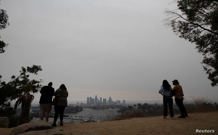 Couples watch downtown from Angels Point at sunset in a smoke haze generated by the Bobcat fire in Los Angeles, California, U.S…