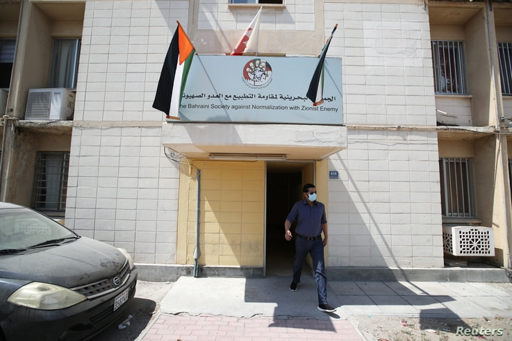 """A man walks out of a building showing an office billboard of """"The Bahraini Society Against Normalization With Zionist Enemy"""" in…"""