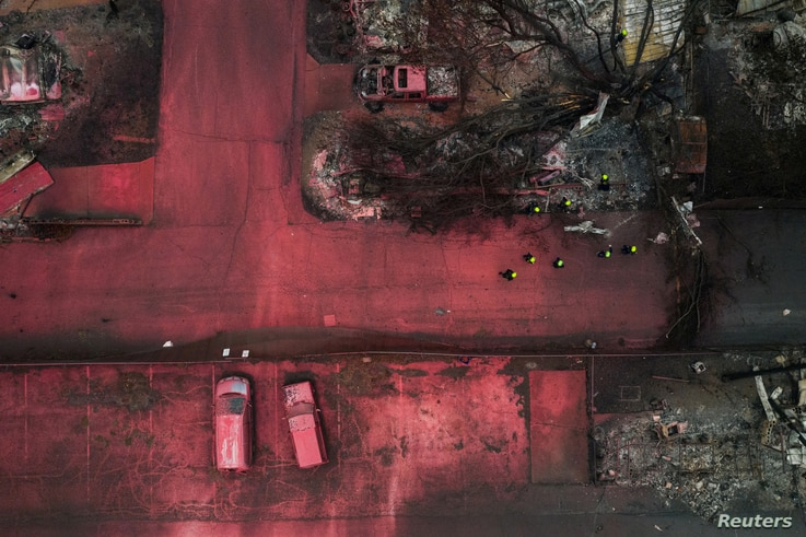 A search and rescue team, surrounded by red fire retardant, looks for victims under burned residences and vehicles in the…