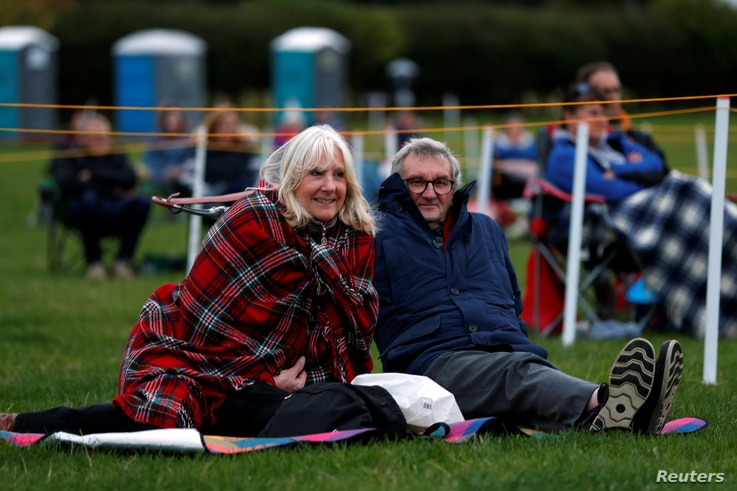 """Spectators keep social distance as they attend the outdoors performance of theatre play """"Voices of The West End"""", at Bywell…"""