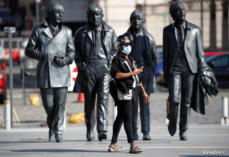 A woman wears a face mask as she stands in front of a statue of The Beatles following the outbreak of the coronavirus disease …