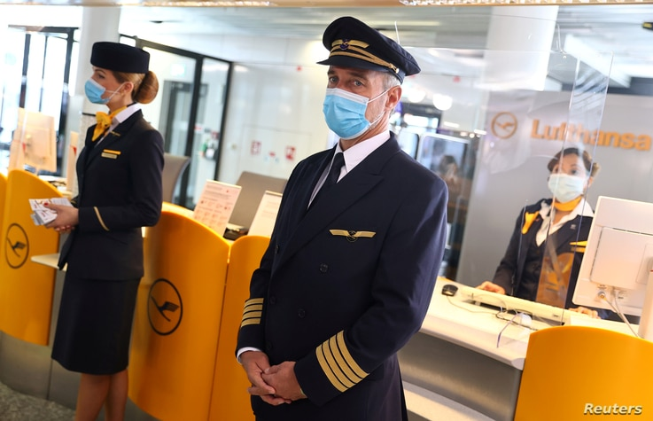 FILE PHOTO: Employees of German airline Lufthansa wear protective masks as they wait for passengers at a boarding gate during a…