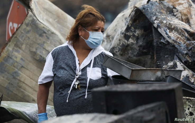 Maria Arevalo searches for items to salvage in the remains of her burned home in a largely Latino neighborhood that was…