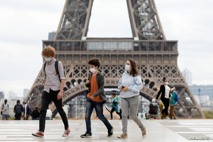 People, wearing protective masks, walk near the Eiffel Tower as the French tourism landmark reopened to visitors after being…
